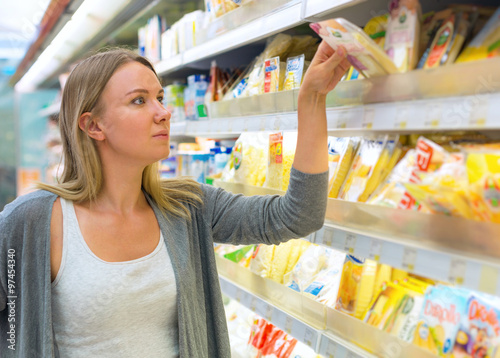 Woman choosing cheese in grocery store.