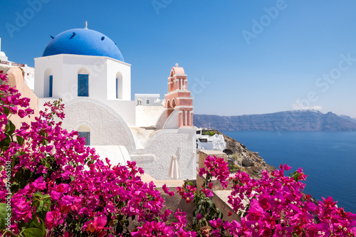 Foto auf Leinwand Santorini Scenic view of traditional cycladic houses with flowers in foreg