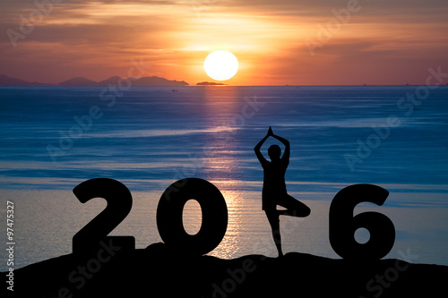 Fotografia  Silhouette young woman play Yoga on the sea and 2016 years while celebrating new
