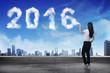 Business woman spraying white 2016 year cloud shape