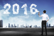 Business man spraying white 2016 year cloud shape