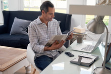 Smiling Man Reading Business Magazine At Home Office Desk
