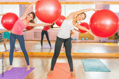 Plakat Piękne wielorasowe kobiety robi ćwiczenia z gimnastyczne piłkę.