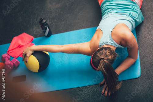 plakat Woman worming up and stretching her body at the gym.Pilates.