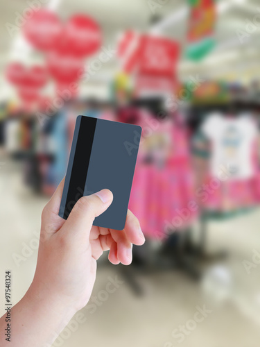 Hand Holding Credit Card With Clothing Store Blurred Background