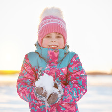 Cute Smiling Preschool Age Girl Holding Snow On Winter Background