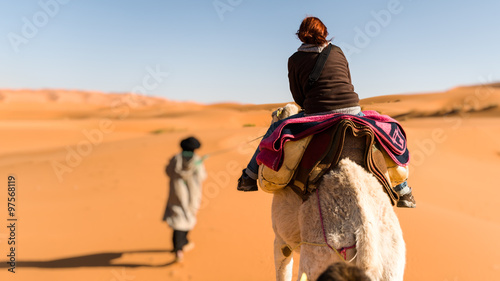 Poster Maroc Woman traveling on camel led by a berber nomad, back view