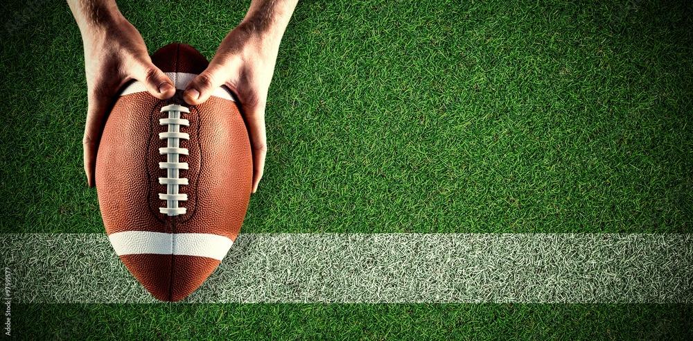 Fototapeta Composite image of american football player holding up football