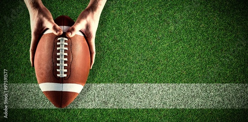 Obraz Composite image of american football player holding up football - fototapety do salonu