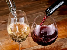 Red And White Wine Pouring On Old Wooden Table