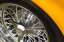 Close-up Of Spoke Wheel Of A Yellow Shiny Classic Vintage Car