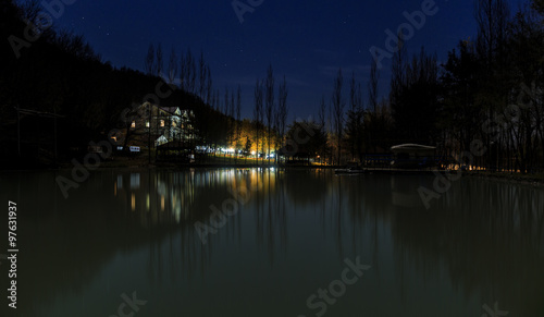 Deurstickers Reflectie Reflected house in a lake at night in the mountains
