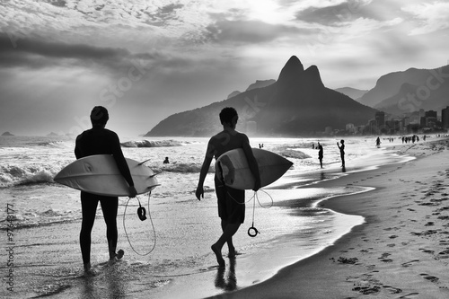 Scenic black and white view of Rio de Janeiro, Brazil with Brazilian surfers walking along the shore of Ipanema Beach #97643177
