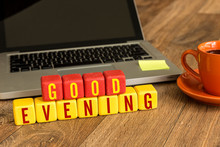 Good Evening Written On A Wooden Cube In A Office Desk