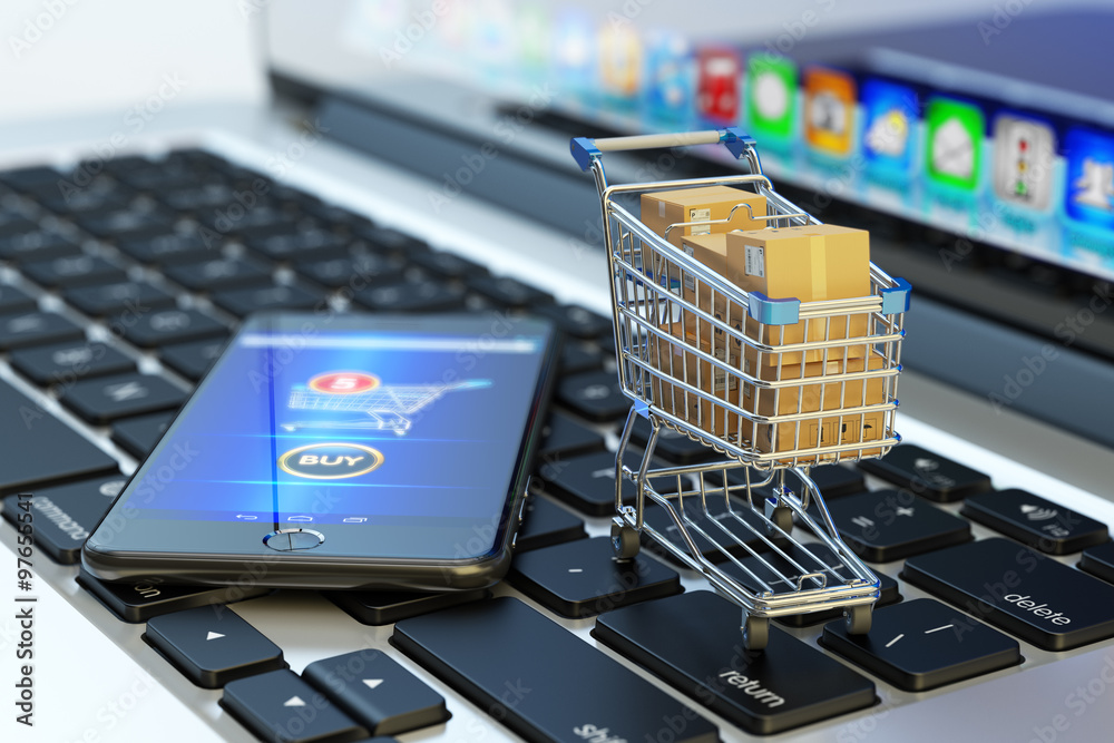 Fototapeta Online shopping, internet purchases and e-commerce concept, modern mobile phone with buy button on the screen and shopping cart full of package boxes on computer laptop keyboard