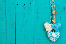 Skeleton Key And Three Rope Hearts Hanging On Teal Blue Door
