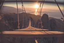 Rope Ladder Over Abyss Leading To A Catholic Cross During Sunrise