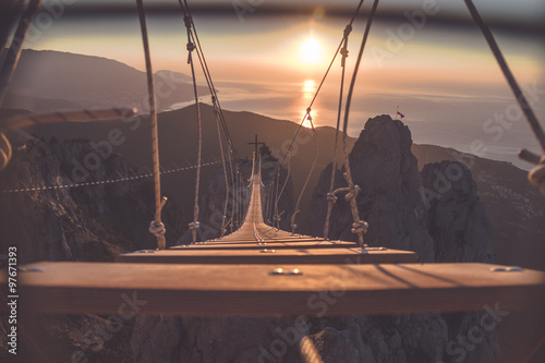 Rope ladder over abyss leading to a catholic cross during sunrise Canvas Print