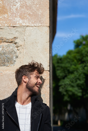 Handsome young man wearing black jacket against stone wall