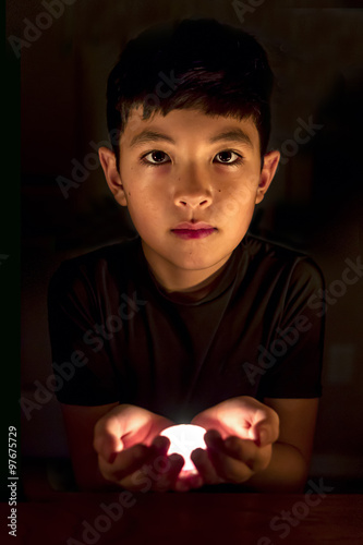 Fotografie, Obraz  Boy holds candle in the dark.