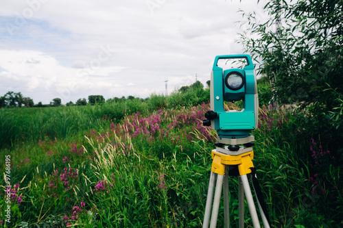 Fotografie, Obraz  Blue geodetické vybavení totální stanice na pozadí louky
