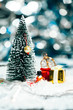 miniature Christmas tree, snowman and gifts in the snow
