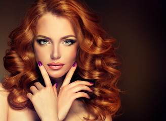 FototapetaGirl model with long red wavy hair. Big curls on the red head . Hairstyle permanent waving