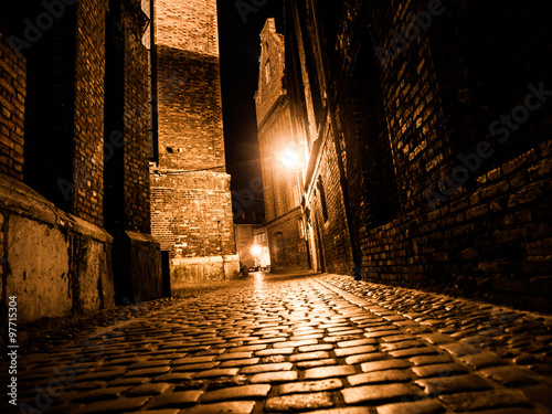 Obraz na plátne Illuminated cobbled street in old city by night