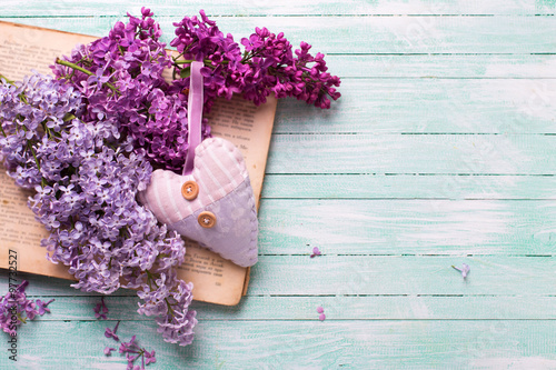 Background  with fresh lilac flowers on open vintage book and he