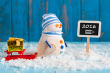 New Year 2016 Is Coming Concept. Snowman With Red Sled And Xmas Giftnear Roadsign 2016. Christmas, New Year Decorations