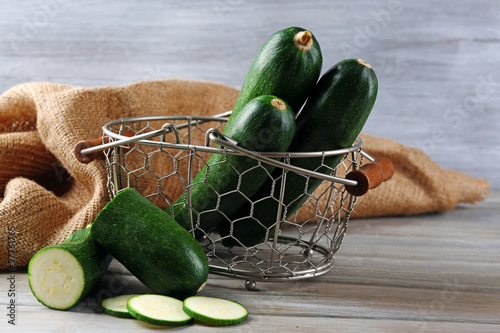 Valokuva  Fresh zucchini in wicker basket on wooden background