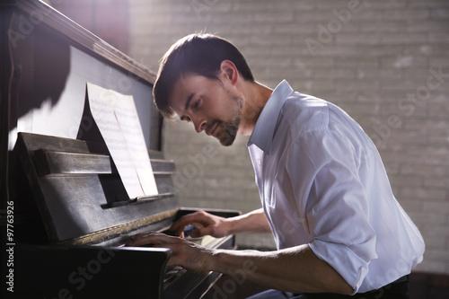 Fotografia Handsome man plays piano in the class