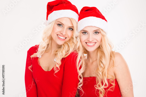 Photo  Beautiful cheerful sisters twins in santa claus clothes and hats