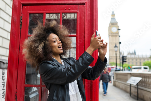 Young woman portrait close to red telephone box in London taking selfie Canvas Print