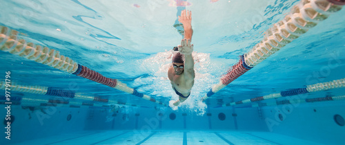 Professional man swimmer inside swimming pool. Underwater panora