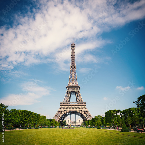 Eiffel Tower and gardens with people walking against blue cloudy sky.