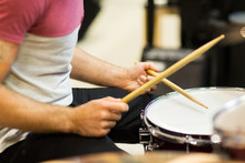 Close Up Of Musician With Drumsticks Playing Drums