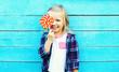 Leinwandbild Motiv Happy smiling child with sweet lollipop having fun over colorful