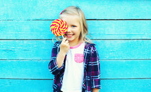 Happy Smiling Child With Sweet Lollipop Having Fun Over Colorful