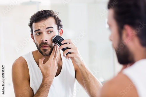 Reflection of concentrated man shaving with electric razor