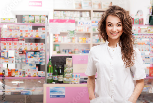 Tuinposter Apotheek Smiling doctor in front of pharmacy desk