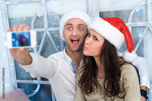 Juliste  Christmas selfie.Young beautiful couple in love is making selfie