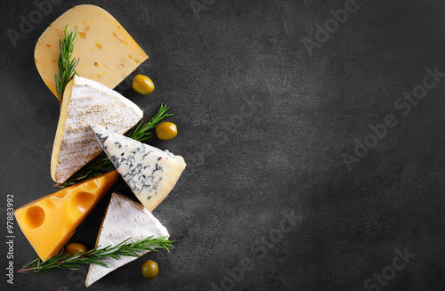 Different kinds of cheese, olives and rosemary on grey background, copy space