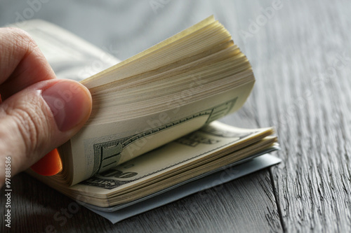 Fotografía man hands counting dollar notes on wood table