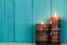 Textured Candles Burning By Teal Blue Background