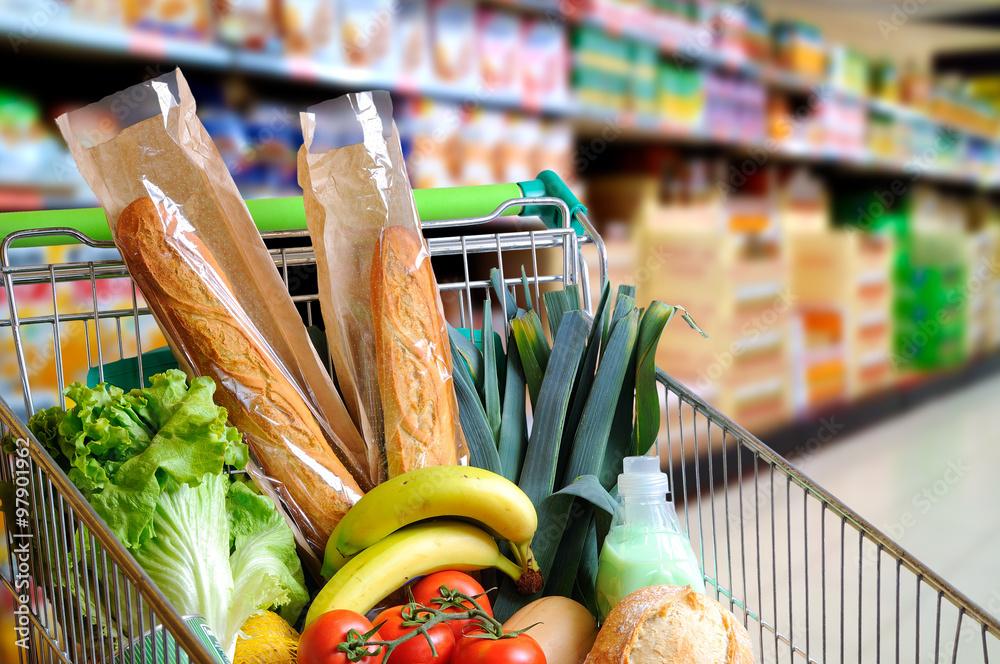 Fototapeta Shopping cart full of food in supermarket aisle elevated view