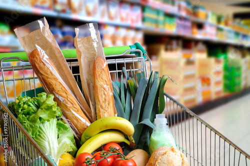 Fotografia Shopping cart full of food in supermarket aisle elevated view