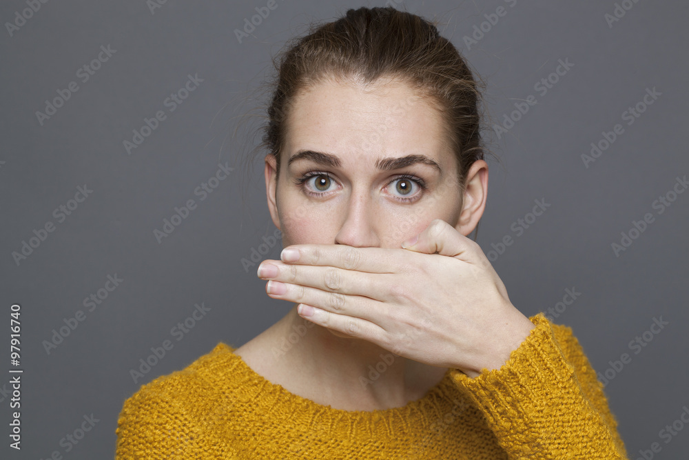 Fototapeta negative feelings concept - portrait of surprised beautiful 20s girl covering her mouth for bad breath or taboo,studio shot on gray background