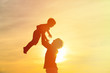canvas print picture - father and little son silhouettes play at sunset