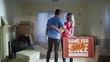 Happy affectionate young couple standing with 'sold' sign in new home
